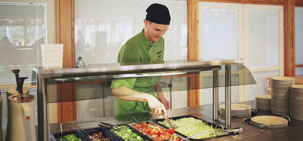 DiakonJuhlan työntekijä asettelee salaatteja valmiiksi lounasta varten.